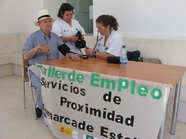 Alumnas del Taller de Empleo tomando la tensión a un anciano