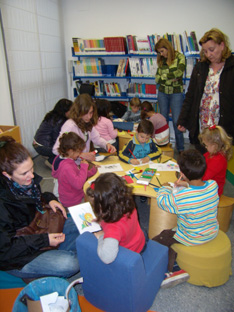 Madres y niños decoran la sala infantil de la Biblioteca Municipal de Lora.