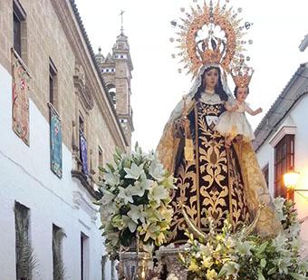 Virgen del Carmen de Osuna con la espadaña de su iglesia al fondo