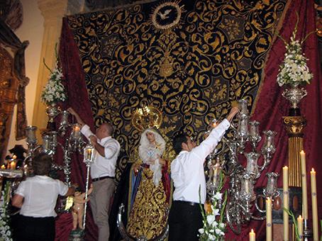 Preparación del altar mayor para el triduo en honor de la Virgen de los Dolores en la parroquia de San Sebastián