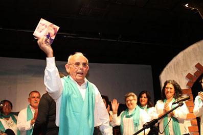 Miembros del coro Atalaya muestran al público el obsequio recibido por la Hermandad