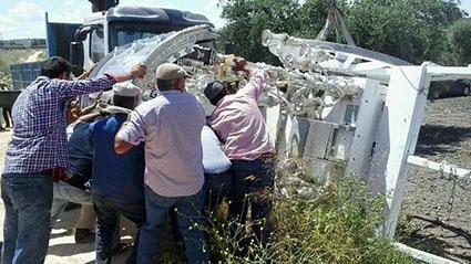 La carreta volcada, intentando ser levantada por los rocieros de Osuna. Foto:  Carmen González / Arahal Información /ABC