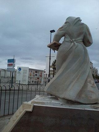 La estatua de la mantecadera de Estepa, con uno de los kioscos informativos al fondo, esta mañana